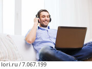 Купить «smiling man with laptop and headphones at home», фото № 7067199, снято 15 марта 2014 г. (c) Syda Productions / Фотобанк Лори