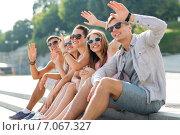Купить «group of smiling friends sitting on city street», фото № 7067327, снято 20 июля 2014 г. (c) Syda Productions / Фотобанк Лори