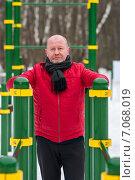 Купить «Пожилой мужчина занимается на брусьях в спортивном городке», эксклюзивное фото № 7068019, снято 23 февраля 2015 г. (c) Игорь Низов / Фотобанк Лори