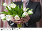 Мужчина в костюме протягивает букет цветов, белые тюльпаны. Стоковое фото, фотограф Pukhov K / Фотобанк Лори