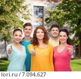 Купить «group of smiling teenagers over campus background», фото № 7094627, снято 22 июня 2014 г. (c) Syda Productions / Фотобанк Лори