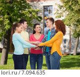 Купить «group of smiling teenagers over campus background», фото № 7094635, снято 22 июня 2014 г. (c) Syda Productions / Фотобанк Лори