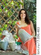 Купить «Woman with fertilizer granules in bag», фото № 7096483, снято 26 апреля 2018 г. (c) Яков Филимонов / Фотобанк Лори