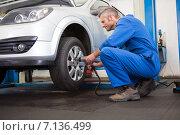 Mechanic adjusting the tire wheel. Стоковое фото, агентство Wavebreak Media / Фотобанк Лори