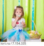 Девочка сидит на деревянном ящике с корзинкой пасхальных яиц. Стоковое фото, фотограф Евгения Устиновская / Фотобанк Лори