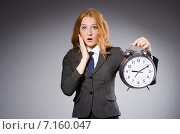 Купить «Businesswoman with clock being late for her deliverables», фото № 7160047, снято 20 декабря 2013 г. (c) Elnur / Фотобанк Лори