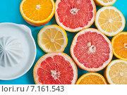 Разные цитрусовые на голубом столе рядом с соковыжималкой. Стоковое фото, фотограф Anna Alferova / Фотобанк Лори