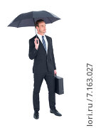Купить «Businessman sheltering under umbrella holding briefcase», фото № 7163027, снято 25 марта 2019 г. (c) Wavebreak Media / Фотобанк Лори