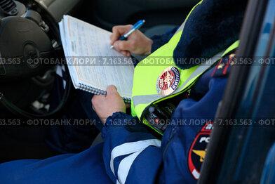 Сотрудник ГИБДД сидя в машине выписывает штраф за нарушение правил дорожного движения