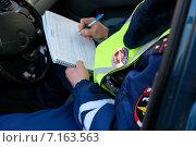 Купить «Сотрудник ГИБДД сидя в машине выписывает штраф за нарушение правил дорожного движения», эксклюзивное фото № 7163563, снято 20 марта 2015 г. (c) Яна Королёва / Фотобанк Лори