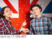 Купить «Девушка с микрофоном и молодой человек в шляпе пожимают друг другу руки на фоне флага Великобритании», фото № 7164407, снято 15 декабря 2014 г. (c) Вячеслав Николаенко / Фотобанк Лори