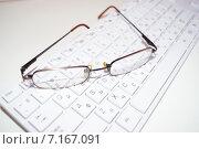 Очки лежат на компьютерной клавиатуре. Стоковое фото, фотограф Юлия Лифарева / Фотобанк Лори