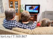 Купить «Родители с ребенком сидят на диване и смотрят телевизор», фото № 7169867, снято 22 декабря 2014 г. (c) Кекяляйнен Андрей / Фотобанк Лори