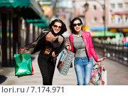 Купить «Две девушки с пакетами покупок идут по улице», фото № 7174971, снято 17 марта 2015 г. (c) Константин Тронин / Фотобанк Лори