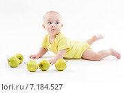 Маленький ребенок лежит на полу среди зеленых яблок. Стоковое фото, фотограф Иван Траймак / Фотобанк Лори