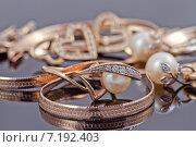 Купить «Золотые украшения на отражающей поверхности: кольца, серьги и цепочки», фото № 7192403, снято 16 марта 2015 г. (c) Сергей Сергеев / Фотобанк Лори