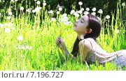 Девочка лежит в траве и дует на букет белых одуванчиков в её руке. Стоковое видео, видеограф Sanda Stanca / Фотобанк Лори