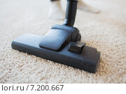 close up of vacuum cleaner cleaning carpet at home. Стоковое фото, фотограф Syda Productions / Фотобанк Лори