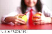 Купить «Школьница выбирает между яблоком и апельсином, а потом берёт себе оба фрукта», видеоролик № 7202195, снято 4 февраля 2011 г. (c) Sanda Stanca / Фотобанк Лори