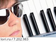 Портрет молодого человека в солнцезащитных очках на фоне клавишного электронного музыкального инструмента. Стоковое фото, фотограф Alexey Matushkov / Фотобанк Лори