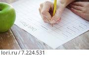 Купить «close up of young woman writing diet plan at home», видеоролик № 7224531, снято 20 марта 2015 г. (c) Syda Productions / Фотобанк Лори
