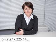 Портрет деловой женщины на рабочем месте. Брюнетка сидит за столом на фоне окна с жалюзи. Стоковое фото, фотограф Александр Лычагин / Фотобанк Лори