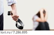 Домашнее насилие и агрессия в семье - злой мужчина с ремнем в руке и закрывшая голову руками женщина. Стоковое фото, фотограф Илья Андриянов / Фотобанк Лори