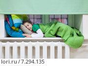 Купить «Девочка спит на подоконнике над батареей, укрывшись зеленым пледом», фото № 7294135, снято 19 апреля 2015 г. (c) Кекяляйнен Андрей / Фотобанк Лори