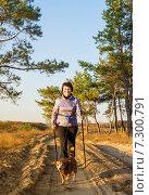 Купить «Довольная женщина с палками для ходьбы и собакой на прогулке по лесу», фото № 7300791, снято 21 июня 2018 г. (c) Светлана Кузнецова / Фотобанк Лори