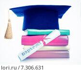 Купить «Шапочка выпускника на стопке книг и диплом об образовании на белом фоне», фото № 7306631, снято 27 марта 2015 г. (c) Валерия Потапова / Фотобанк Лори
