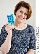 Купить «Улыбающаяся женщина среднего возраста держит в руке упаковку таблеток», фото № 7308203, снято 24 апреля 2015 г. (c) Володина Ольга / Фотобанк Лори