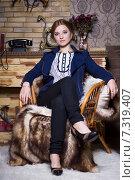 Купить «Красивая девушка сидит в кресле на меховом пледе», фото № 7319407, снято 6 ноября 2014 г. (c) Сергей Сухоруков / Фотобанк Лори