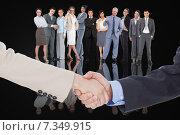 Купить «Composite image of smiling business people shaking hands while looking at the camera», фото № 7349915, снято 25 марта 2019 г. (c) Wavebreak Media / Фотобанк Лори