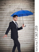 Купить «Composite image of concentrated businessman holding umbrella while stepping», фото № 7367259, снято 21 октября 2018 г. (c) Wavebreak Media / Фотобанк Лори
