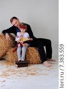 Отец с девочкой в украинской национальной одежде сидят на сене и читают книги. Стоковое фото, фотограф Olena Kravchuk / Фотобанк Лори