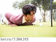Купить «Golfer trying to flick ball into hole», фото № 7384315, снято 21 октября 2014 г. (c) Wavebreak Media / Фотобанк Лори