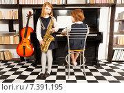Купить «Две девочки в платьях играют на музыкальных инструментах», фото № 7391195, снято 20 февраля 2015 г. (c) Сергей Новиков / Фотобанк Лори