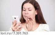 Купить «Молодая женщина пользуется смартфоном, листает страницы в интернете и пишет сообщения, серый фон», видеоролик № 7391763, снято 8 марта 2015 г. (c) Кекяляйнен Андрей / Фотобанк Лори