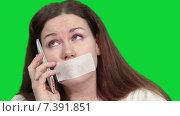 Купить «Женщина с заклеенным ртом пытается разговаривать по сотовому телефону, зеленый изолированный фон», видеоролик № 7391851, снято 4 марта 2015 г. (c) Кекяляйнен Андрей / Фотобанк Лори