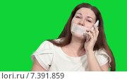 Купить «Женщина разговаривает по сотовому телефону с кляпом во рту, зеленый изолированный фон», видеоролик № 7391859, снято 4 марта 2015 г. (c) Кекяляйнен Андрей / Фотобанк Лори