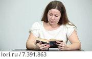 Купить «Сосредоточенная девушка читает книгу за столом», видеоролик № 7391863, снято 4 марта 2015 г. (c) Кекяляйнен Андрей / Фотобанк Лори