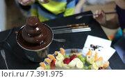 Дети едят фрукты в шоколаде из фонтана. Стоковое видео, видеограф Кекяляйнен Андрей / Фотобанк Лори