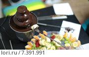 Кусочек банана на длинной вилке макается в жидкий шоколад из фонтана. Стоковое видео, видеограф Кекяляйнен Андрей / Фотобанк Лори