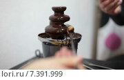 Жидкий шоколад переливающийся в фонтане и руки с кусочком фрукта на вилке, крупный план. Стоковое видео, видеограф Кекяляйнен Андрей / Фотобанк Лори