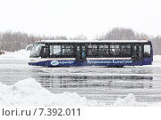 Аэродромный автобус для перевозки пассажиров везет людей к зданию аэровокзала аэропорта Петропавловск-Камчатский во время сильного снегопада (2015 год). Редакционное фото, фотограф А. А. Пирагис / Фотобанк Лори