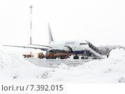 Службы аэродромно-технического обеспечения обслуживают самолет Boeing-767 в аэропорту Петропавловск-Камчатский (аэропорт Елизово) во время снегопада (2015 год). Редакционное фото, фотограф А. А. Пирагис / Фотобанк Лори