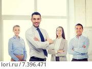 Купить «smiling businessman in office with team on back», фото № 7396471, снято 5 апреля 2014 г. (c) Syda Productions / Фотобанк Лори