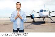 Купить «man praying over airplane on runway background», фото № 7397727, снято 3 февраля 2015 г. (c) Syda Productions / Фотобанк Лори