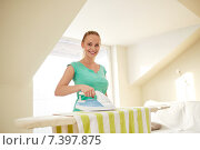 Купить «happy woman with iron and ironing board at home», фото № 7397875, снято 25 января 2015 г. (c) Syda Productions / Фотобанк Лори