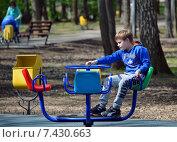 Купить «Мальчик-подросток катается один на карусели в городском парке», эксклюзивное фото № 7430663, снято 9 мая 2015 г. (c) Александр Замараев / Фотобанк Лори